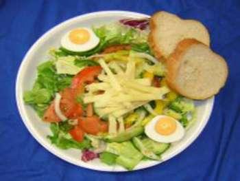 Salatteller mit Käse und Ei, dazu Stangenweißbrot