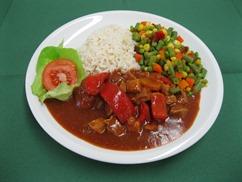 Schweinegulasch mit Paprika mit, Wellenbandnudeln und, Salat an, Dressing Italienische Art