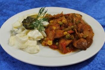 Currywurstpfanne mit Paprika, Mais und Erbsen an hausgemachtem Kartoffelsalat