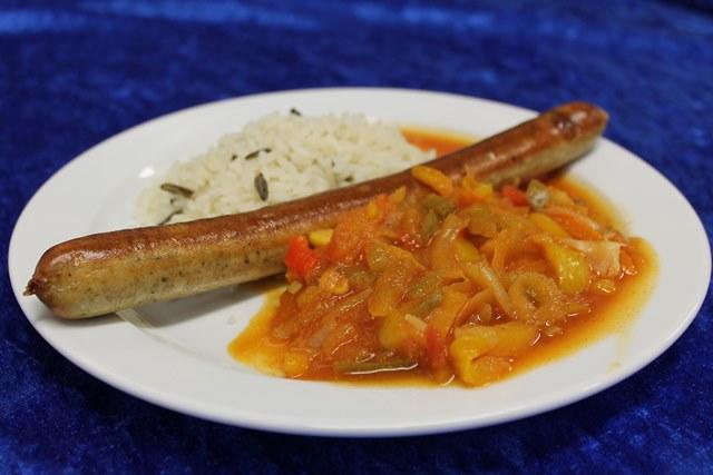 Fleischlose Bratwurst mit buntem Reis und pikanter Paprikasauce