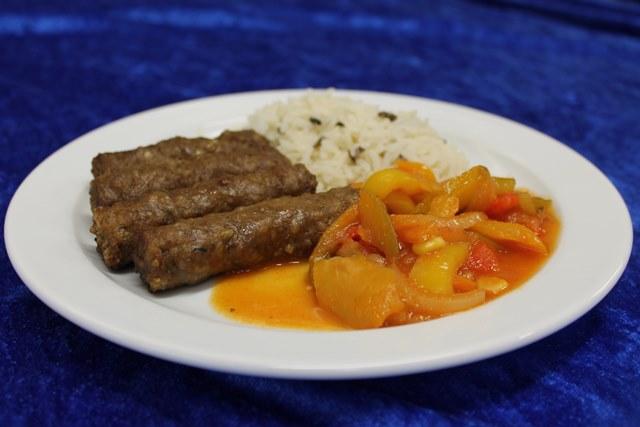 Cevapcici mit buntem Reis und pikanter Paprikasauce