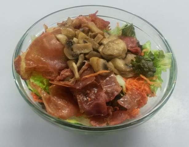 Salatschüssel mit Speckscheiben und Champignons