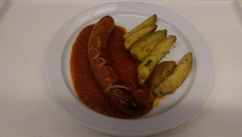 Currywurst mit Ofenkartoffeln, Salat und Dessert